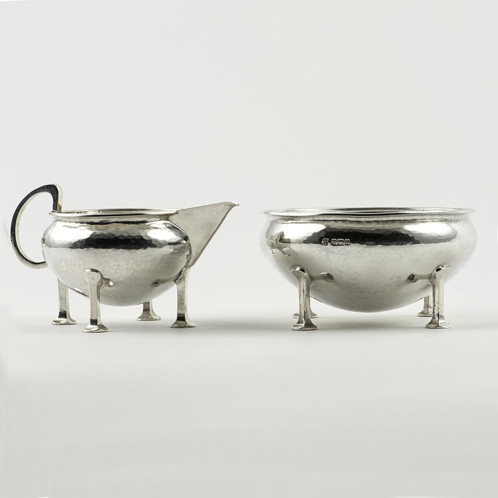 An Arts And Crafts Silver Cream Jug And Sugar Bowl.