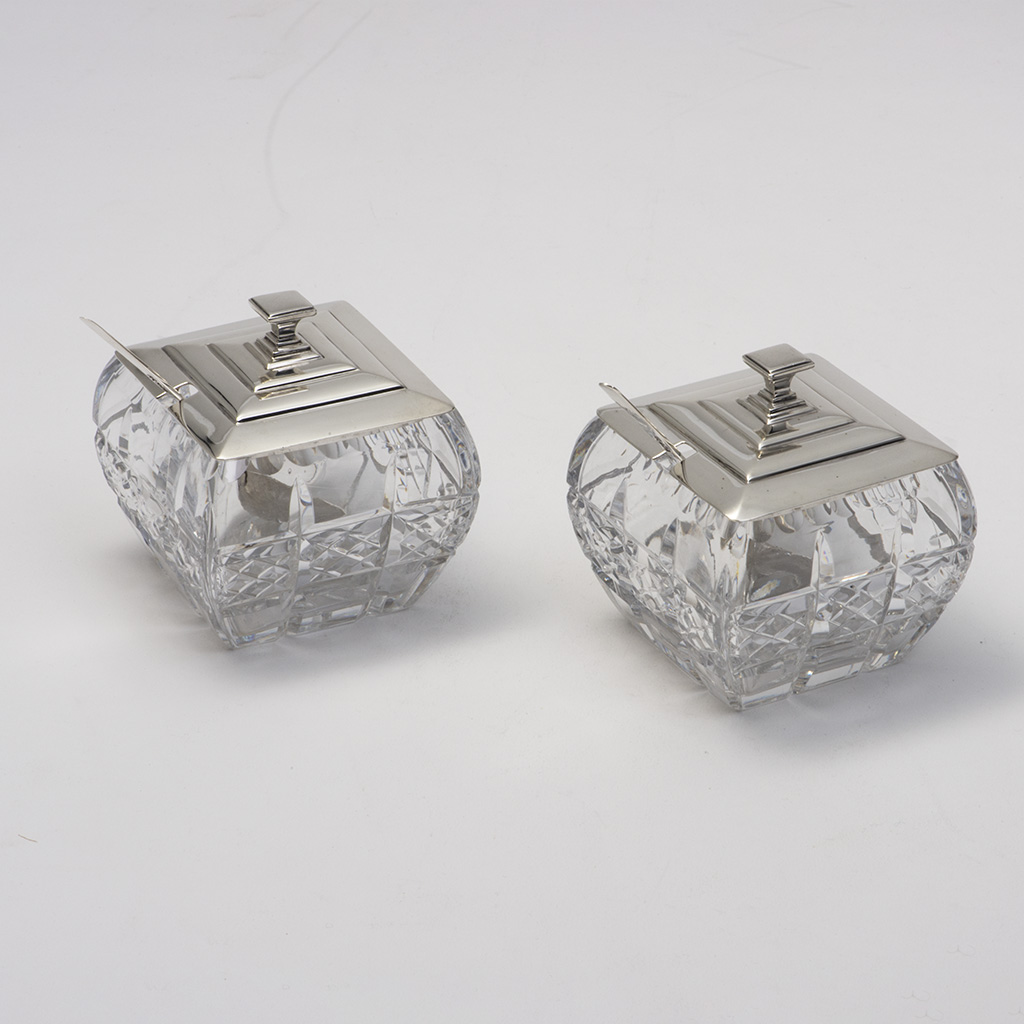 A Pair Of Art Deco Silver And Glass Jam Pots With Spoons.